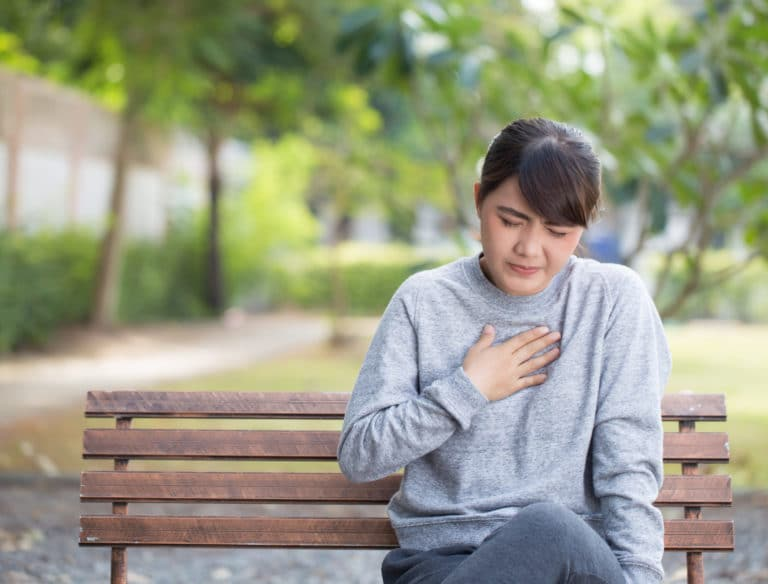 woman with her hand over her chest suffering from acid reflux