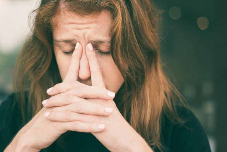 Woman holding her nasal ridge
