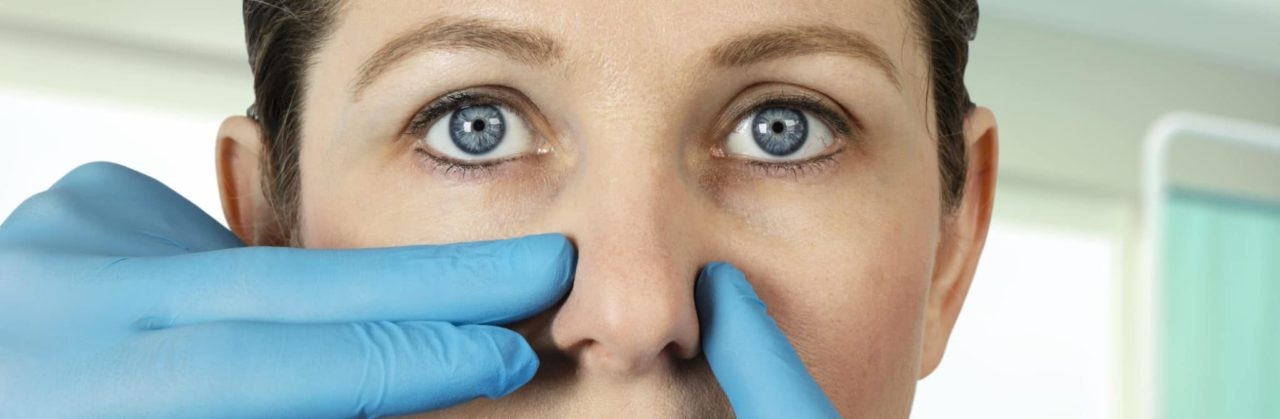 Doctor inspecting woman's nose