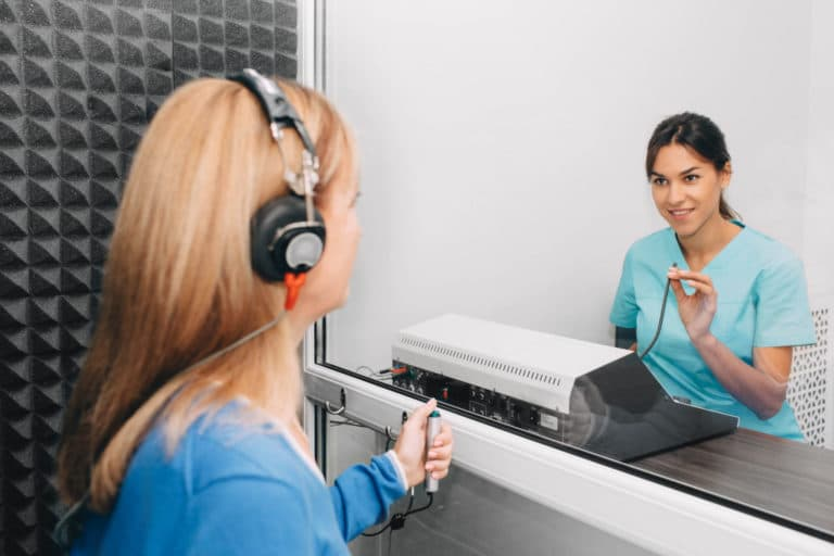 Audiologist conducting pure tone test on patient