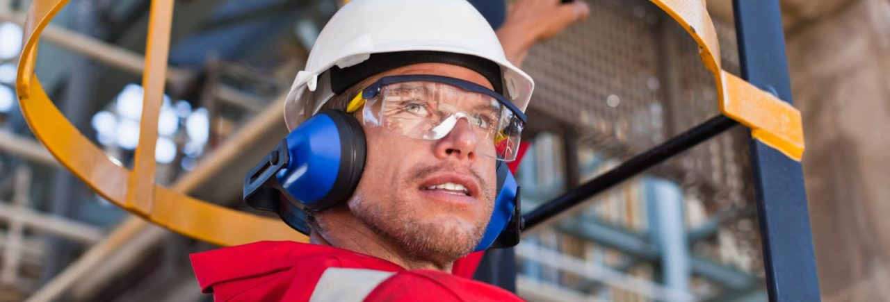 man wearing safety earmuffs, hardhat and safety glasses