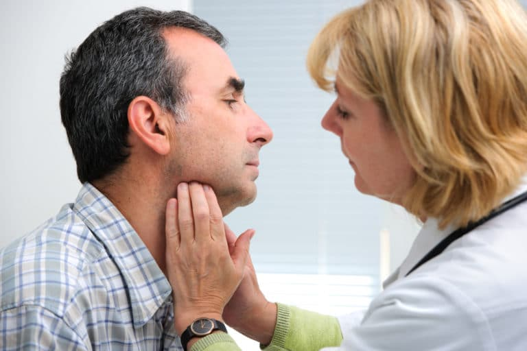 Doctor checking patients thyroids
