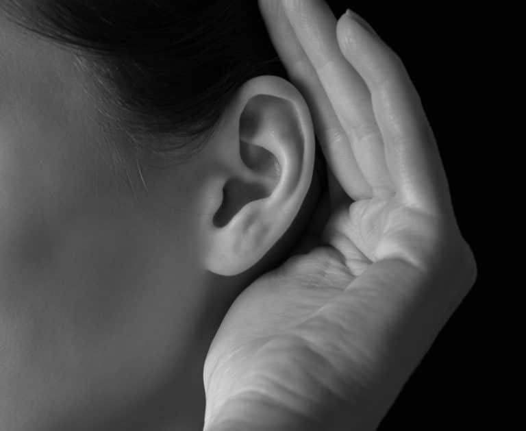 Woman holding her hand to her ear to hear better