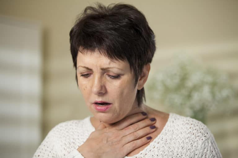 woman with hand over her throat due to soar throat