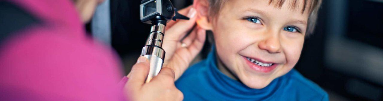 Doctor inspecting boys ear with otoscope