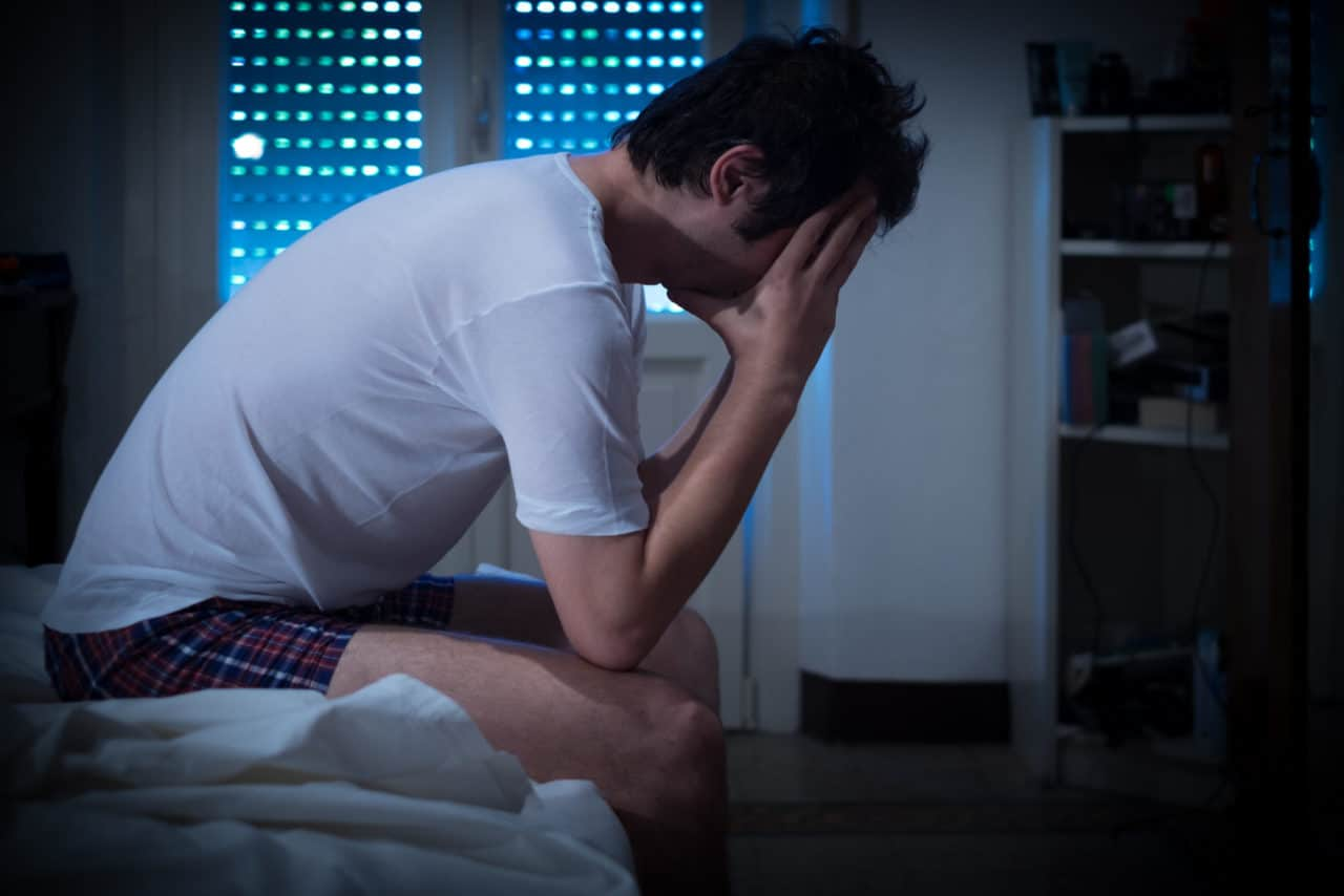 Man sitting up in bed unable to sleep