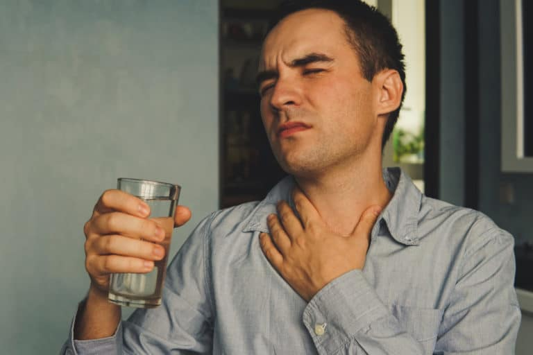 Man wincing from sore throat