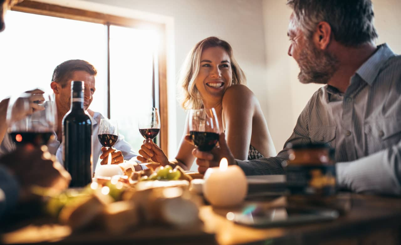 Two couples drinking wine around a table