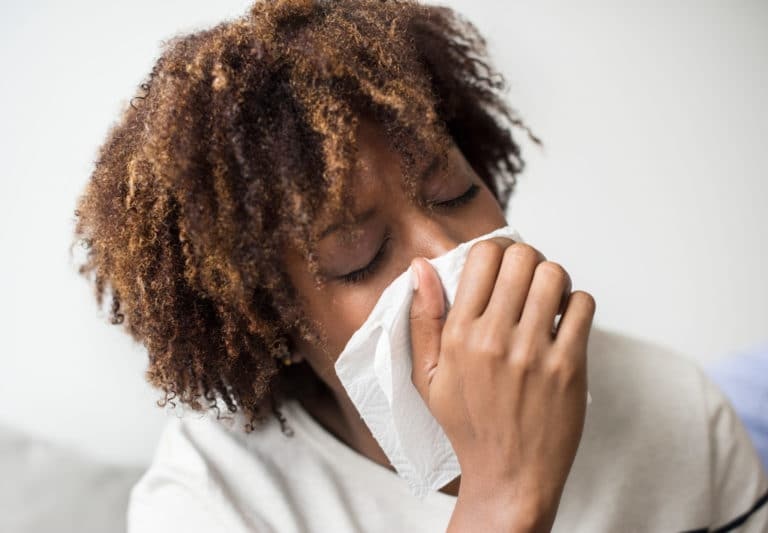Woman sneezing into a tissue