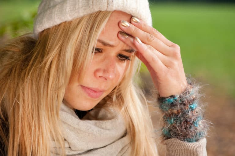Woman looking sad with her hand to her forehead