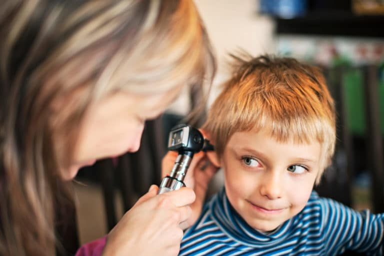 Doctor inspecting child's ear with otoscope
