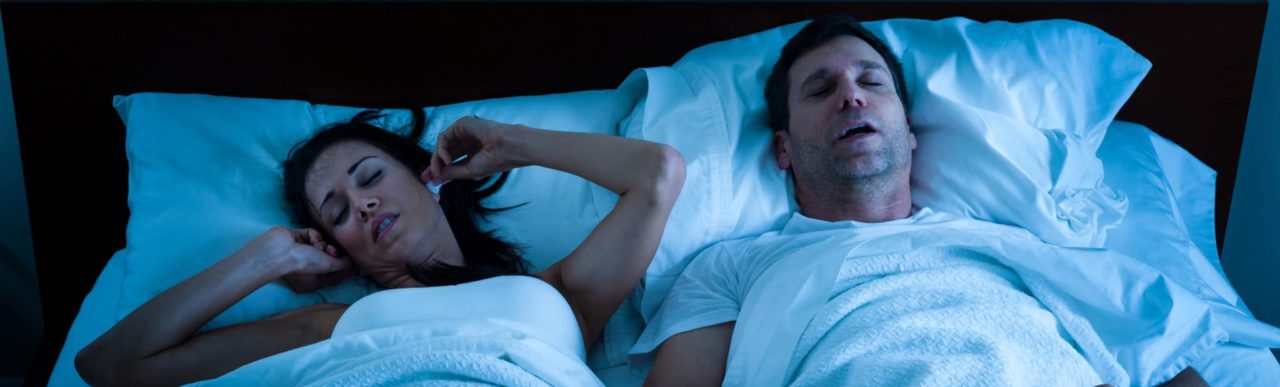 Man snoring in bed while woman plugs ears and tries to sleep